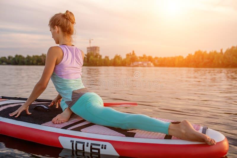 Mulher desportiva na posição da ioga sobre o paddleboard, fazendo a ioga na placa do sup, o exercício para a flexibilidade e o es fotos de stock