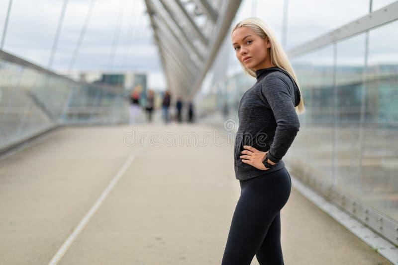 Mulher desportiva no equipamento preto do exercício que está na ponte moderna na cidade foto de stock royalty free