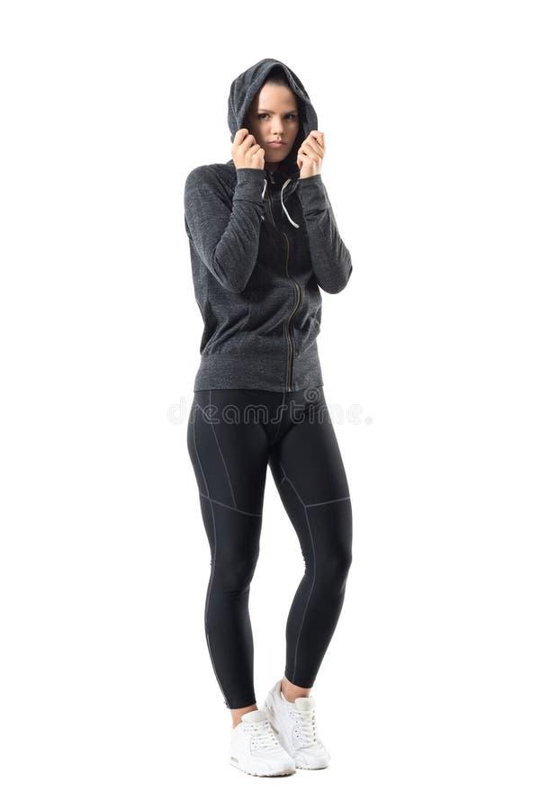 Mulher desportiva no sportswear morno do outono com o hoodie na cabeça que olha a câmera imagens de stock