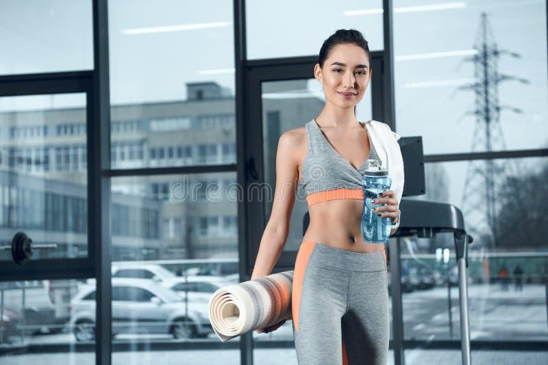 mulher desportiva nova com a esteira e água roladas da ioga imagens de stock