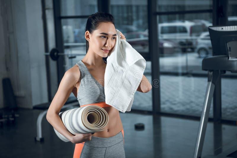 mulher desportiva nova com a limpeza rolada da esteira da ioga suada com a toalha após exercícios imagens de stock