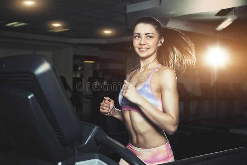 A mulher desportiva nova corre na máquina no gym imagem de stock royalty free