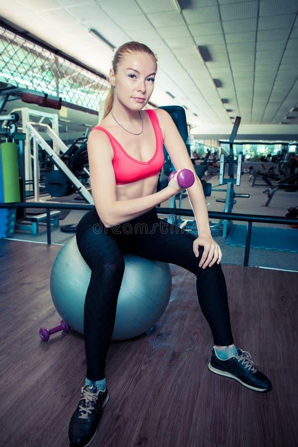 A mulher desportiva nova faz exercícios físicos com peso na ajuste-bola no gym fotografia de stock