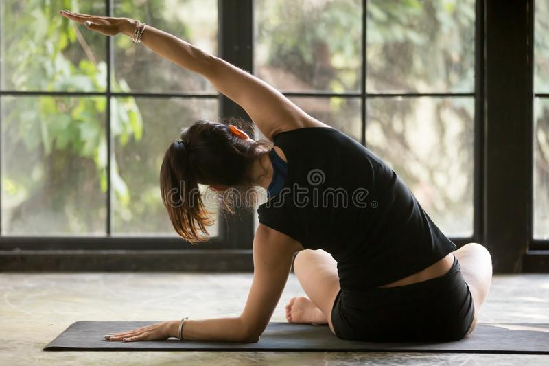 Mulher desportiva nova na pose de dobra lateral de Sukhasana, backgr da janela fotografia de stock