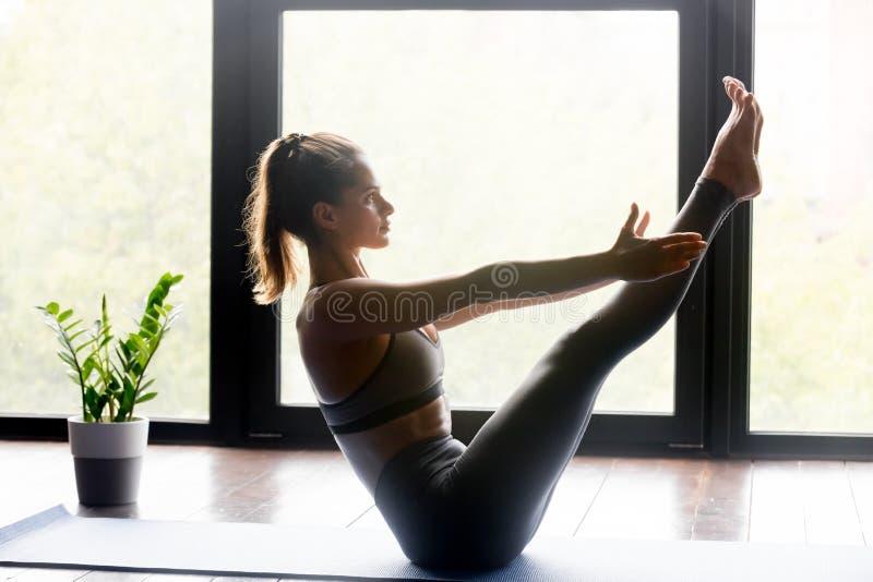 Mulher desportiva nova na pose do equilíbrio para o Abs imagem de stock