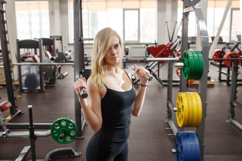 Mulher desportiva nova no gym que levanta com pesos contra muitos simuladores do gym no fundo fotos de stock