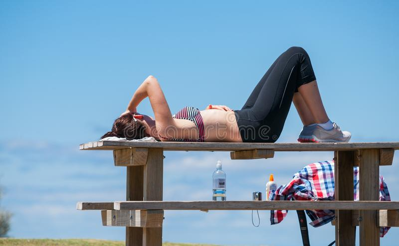 Mulher desportiva nova que descansa após a escalada para cobrir da montanha foto de stock royalty free