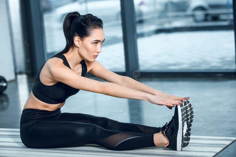 mulher desportiva nova que estica e que alcança para os pés com mãos na esteira da ioga fotografia de stock royalty free