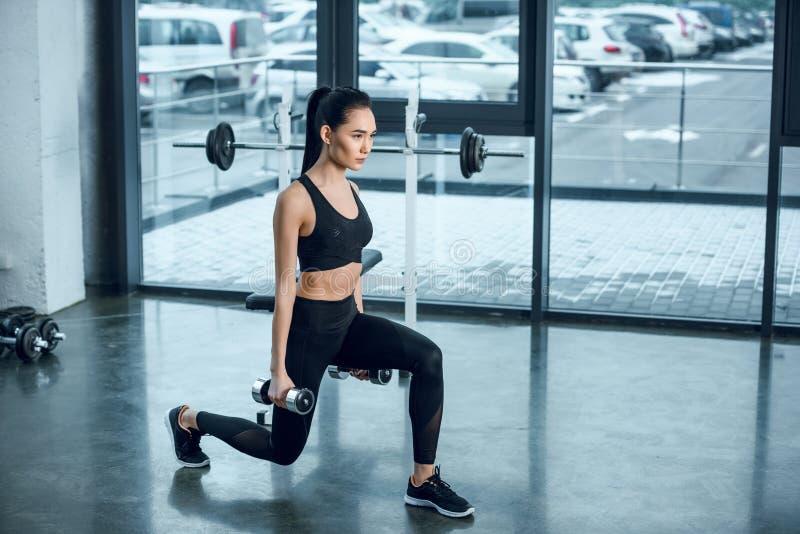 mulher desportiva nova que faz únicas ocupas do pé com pesos fotografia de stock