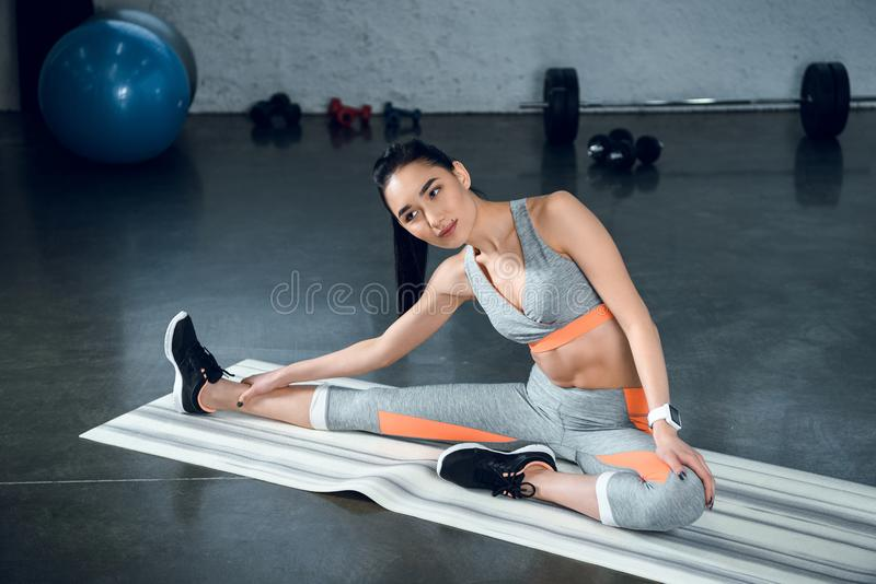 mulher desportiva nova que faz a curvatura lateral na esteira da ioga fotos de stock