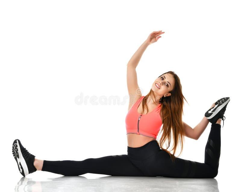 A mulher desportiva nova que faz a ginástica que estica exercícios da aptidão malha na parte superior alaranjada isolada no branc fotografia de stock