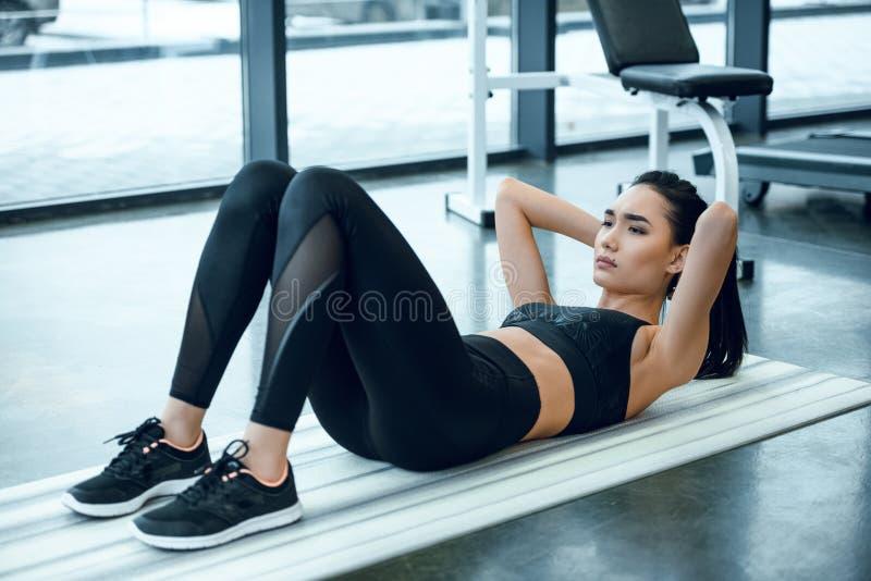 mulher desportiva nova que faz triturações na esteira da ioga imagem de stock