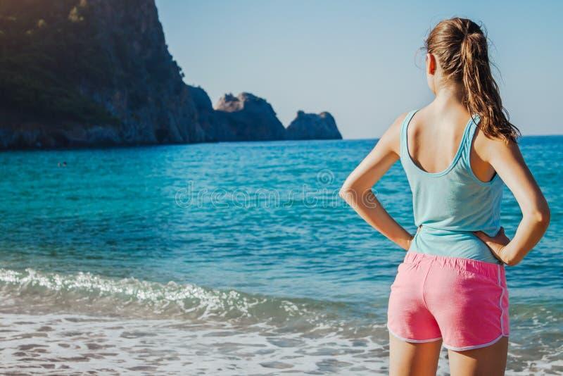Mulher desportiva nova que tem um resto após um exercício na praia imagem de stock