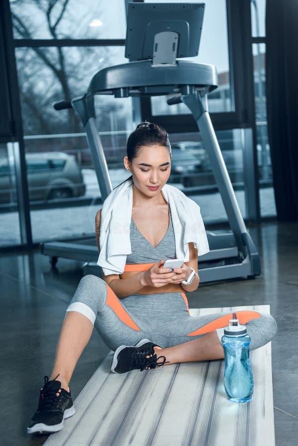 mulher desportiva nova que usa o smartphone ao sentar-se na esteira da ioga imagens de stock