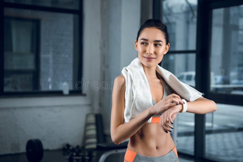 mulher desportiva nova que usa o smartwatch para verificar a atividade fotografia de stock