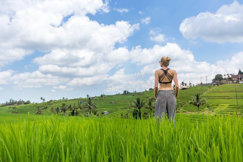 Mulher desportiva ocasional relaxado que aprecia a natureza pura em campos verdes bonitos do arroz em Bali fotografia de stock
