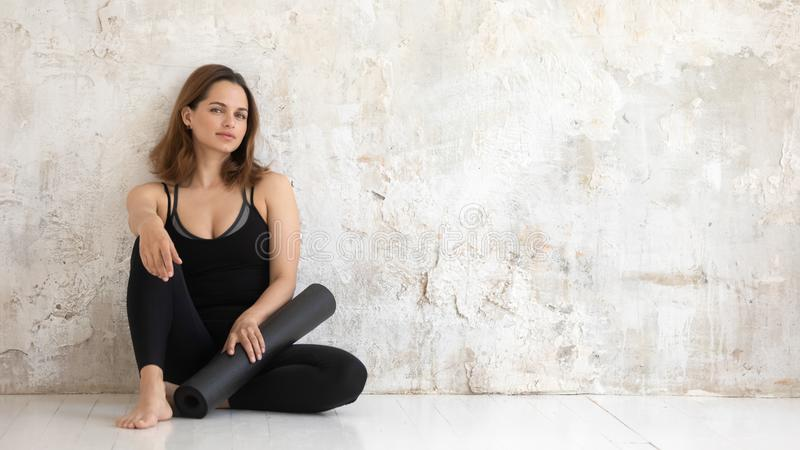 Mulher desportiva que descansa após a carne sem gordura do exercício contra a parede bege do grunge foto de stock royalty free
