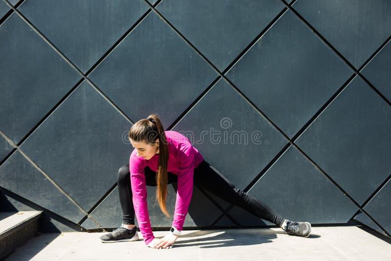 Mulher desportiva que estica e que aquece os pés para correr o exercício urbano do inverno da aptidão Esporte e conceito saudável imagem de stock royalty free