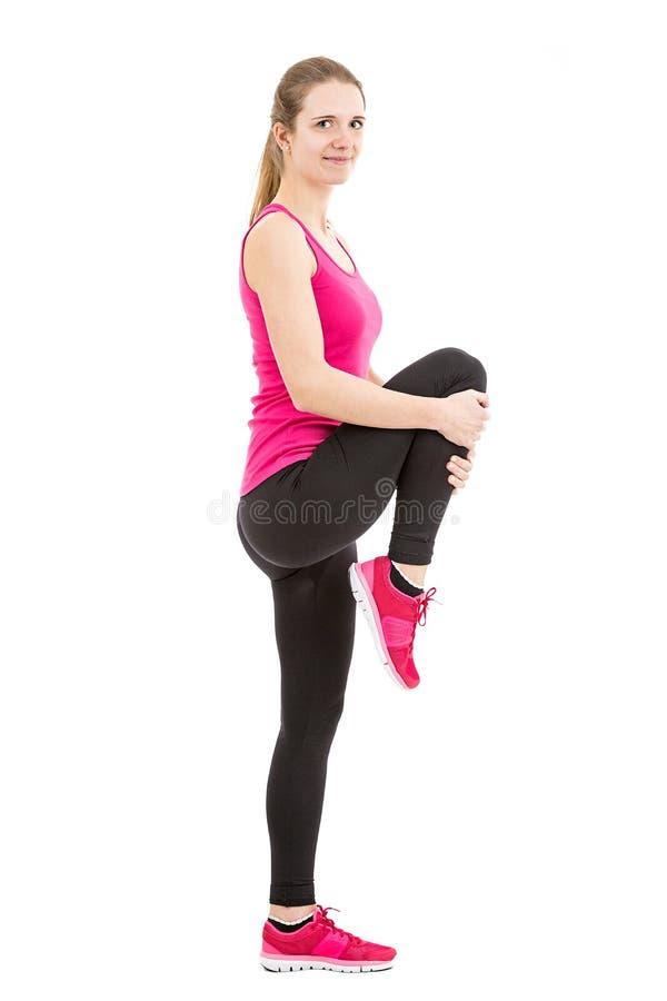 Mulher desportiva que estica seus pés imagem de stock