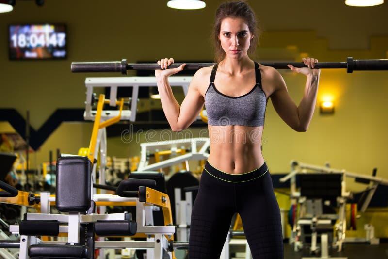 Mulher desportiva que exercita com o barbell no gym imagem de stock