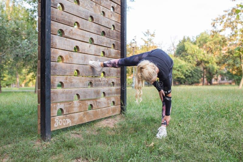 Mulher desportiva que faz esticando o exercício fotografia de stock