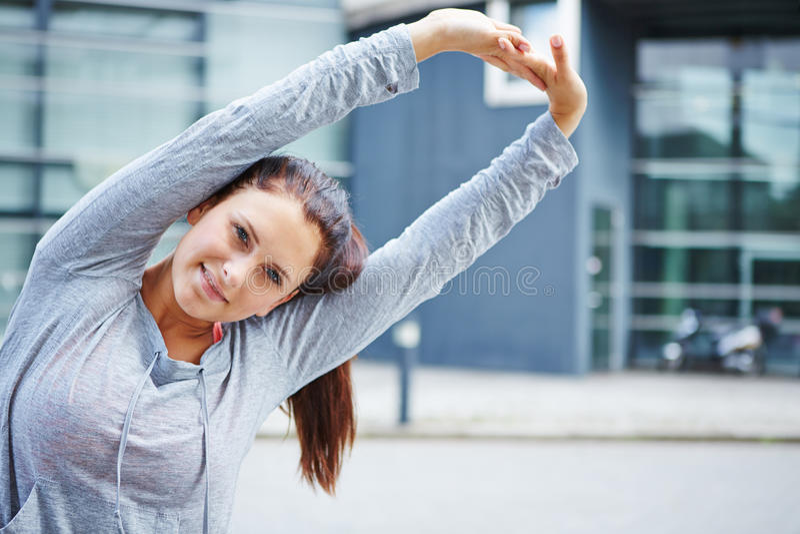 Mulher desportiva que faz esticando o exercício imagens de stock