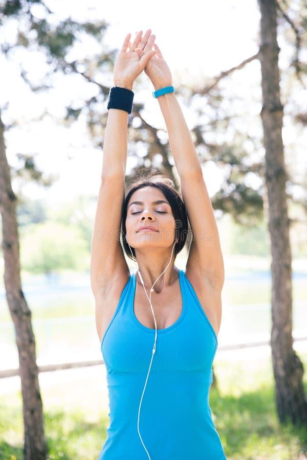 Mulher desportiva que faz esticando o exercício fora fotos de stock royalty free