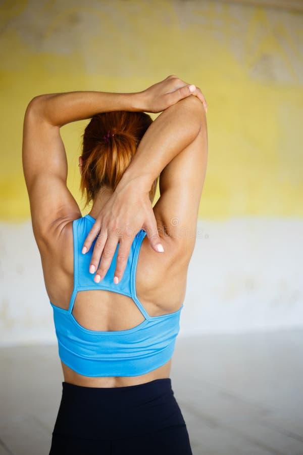 Mulher desportiva que faz a ioga que estica o exercício no gym imagens de stock