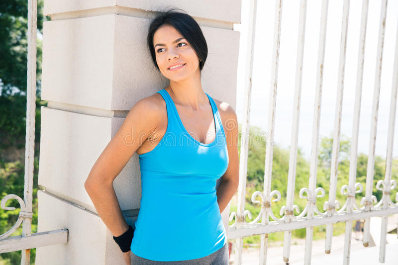 Mulher desportiva que inclina-se na cerca fora fotografia de stock royalty free