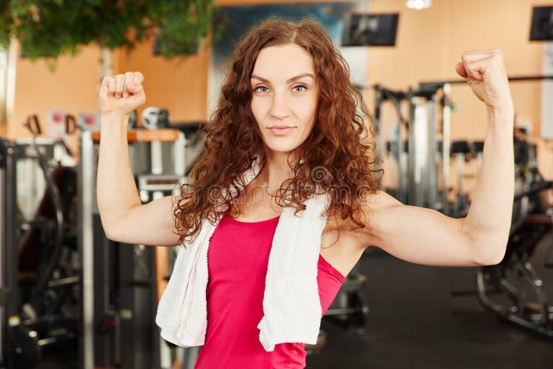 Mulher desportiva que mostra seus músculos imagens de stock
