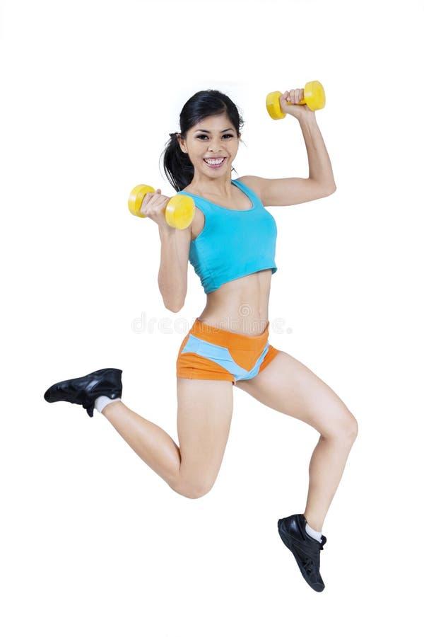 Mulher desportiva que salta com pesos imagens de stock