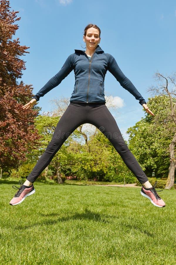 Mulher desportiva que salta no parque fotografia de stock royalty free