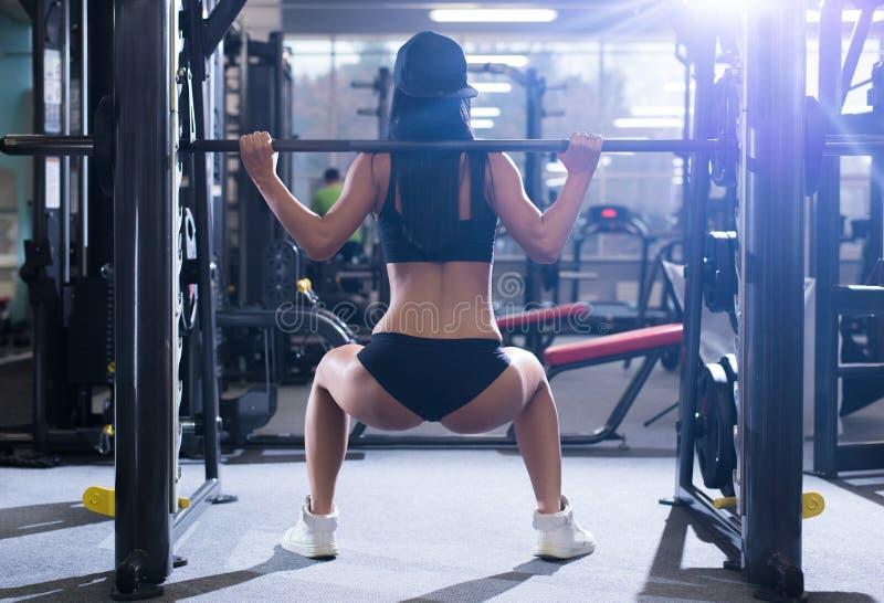 Mulher desportiva 'sexy' que faz o exercício da aptidão do poder no gym do esporte Menina bonita que dá certo no gym fotografia de stock royalty free