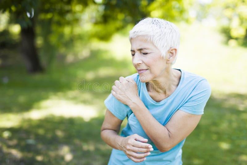 A mulher desportiva superior tem a dor do ombro no parque imagens de stock royalty free