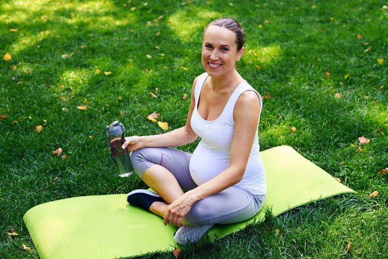 Mulher desportivo grávida relaxado com a garrafa da água que senta-se dentro imagem de stock royalty free