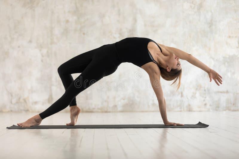 Mulher desportivo nova que faz o exercício de Wild Thing Camatkarasana da ioga fotografia de stock