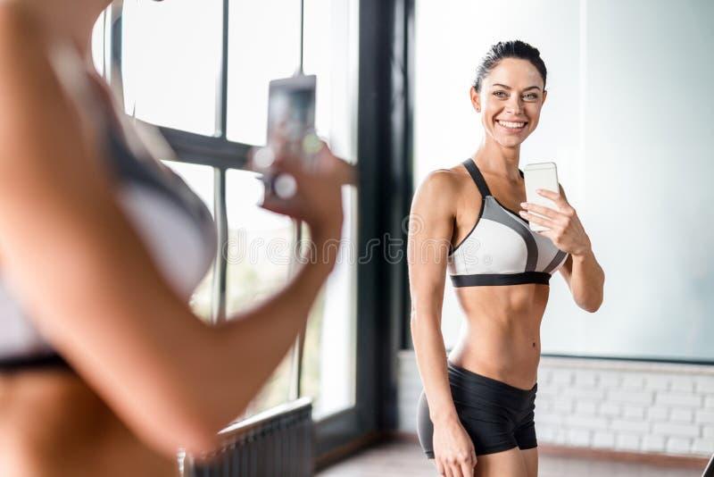 Mulher desportivo nova que toma o espelho Selfie no Gym imagens de stock royalty free