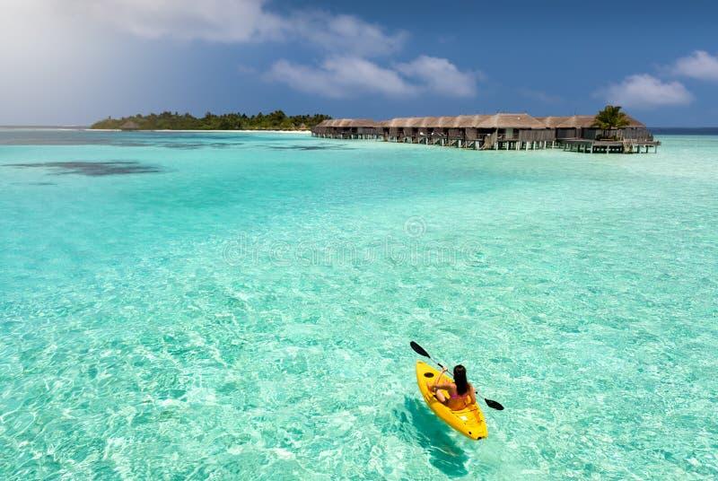 Mulher desportivo que canoeing sobre as águas de Maldivas imagens de stock royalty free
