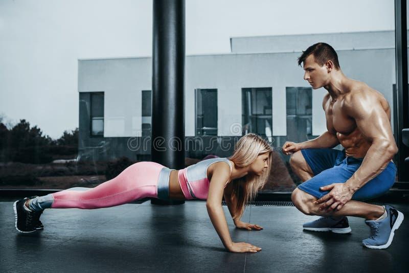 Mulher desportivo que faz o exercício da prancha que treinam para trás e os músculos da imprensa com instrutor Poder da força do  imagem de stock royalty free