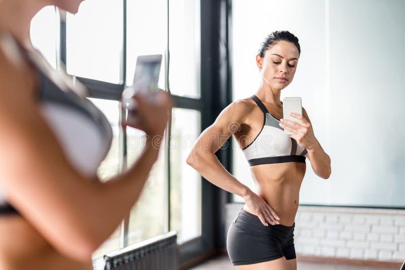 Mulher desportivo que levanta para o espelho Selfie que dobra os músculos fotografia de stock