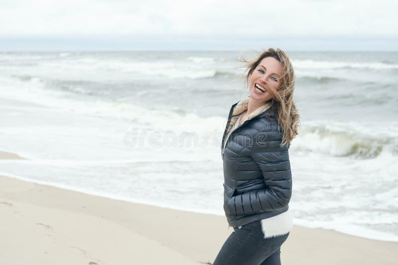 Mulher despreocupada de riso vivo em uma praia windswept imagem de stock