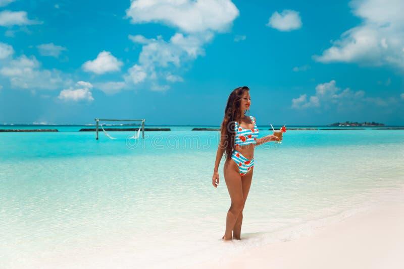Mulher despreocupada do biquini na praia tropical Menina magro bonita com coctail que aprecia na ilha exótica no oceano de turqu foto de stock royalty free