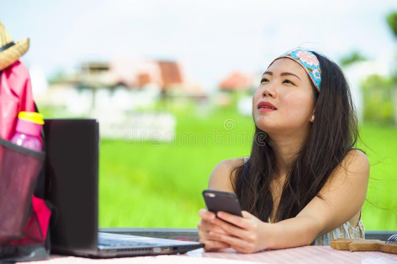 Mulher digital coreana asiática bonita e feliz nova do nômada que trabalha o ar livre relaxado na tabela da cafetaria com laptop  fotografia de stock