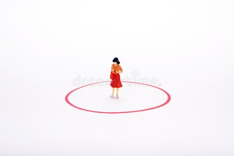 Mulher diminuta do pople no círculo vermelho sobre o contexto ou o backg branco fotografia de stock royalty free