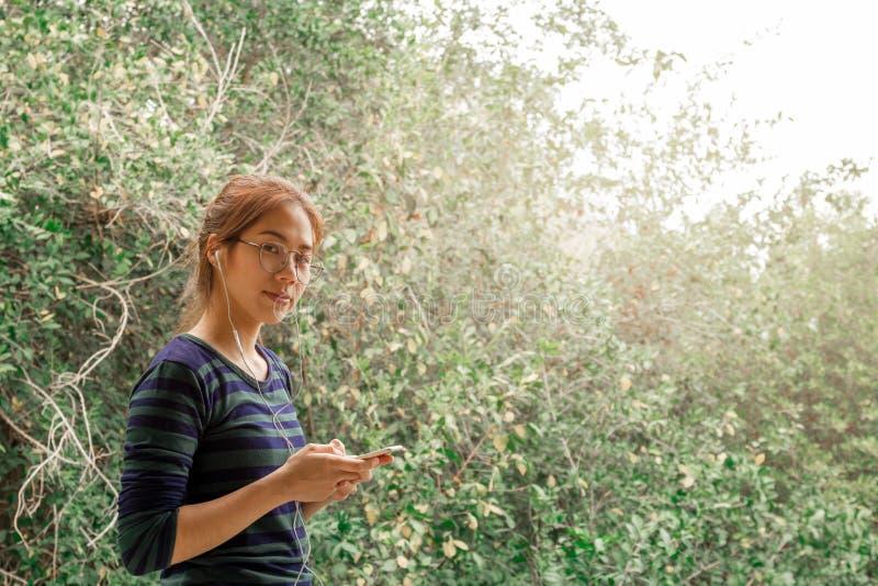 Mulher do adolescente do retrato com vidros dos olhos para escutar a música com fone de ouvido imagem de stock royalty free