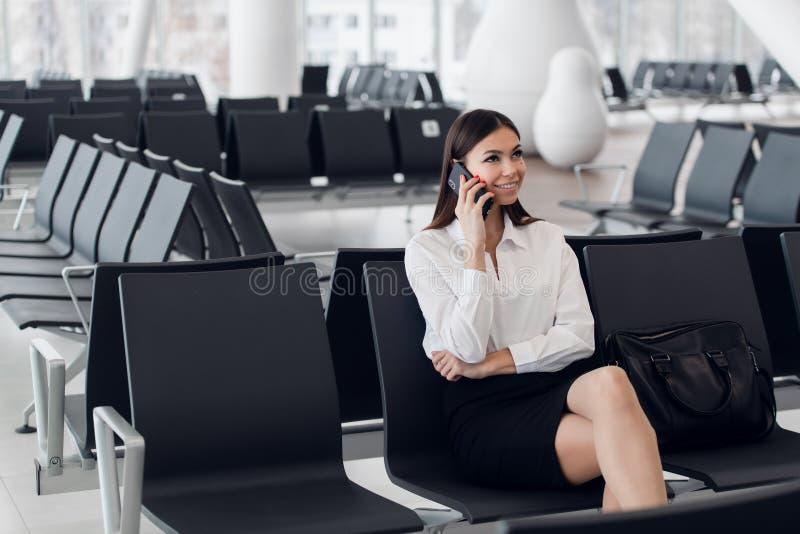 Mulher do aeroporto no telefone esperto na porta que espera no terminal Conceito da viagem a?rea com assento ocasional novo da mu fotografia de stock