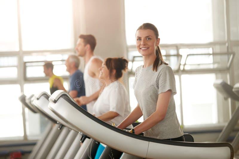Mulher do ajuste que corre na escada rolante que sorri na câmera fotografia de stock royalty free