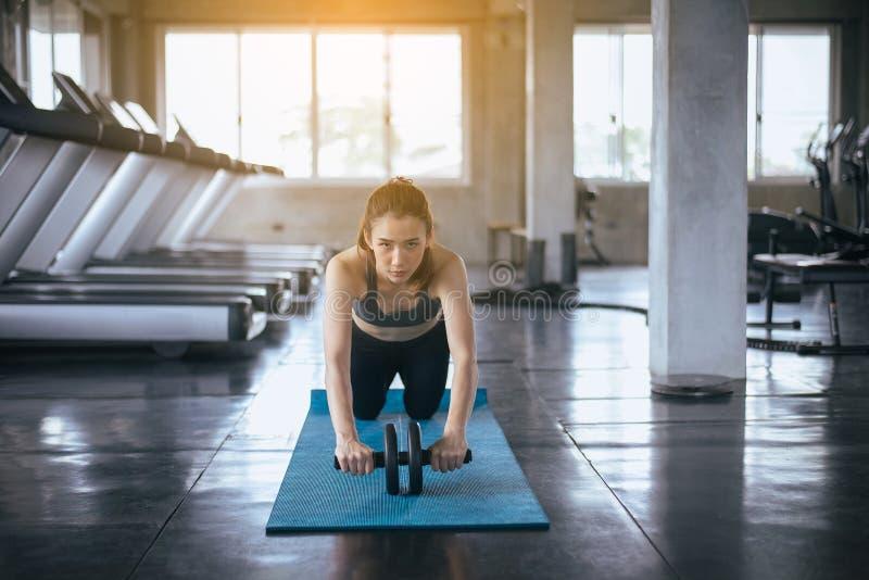 Mulher do ajuste que faz o exercício e o exercício com roda do rolo, esporte individual do equilíbrio imagens de stock royalty free