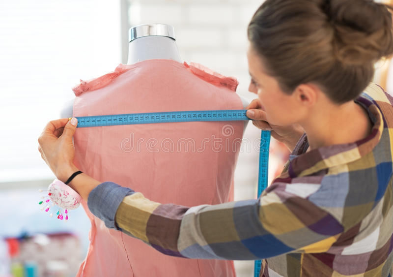 Mulher do alfaiate que trabalha com o vestido no estúdio imagem de stock
