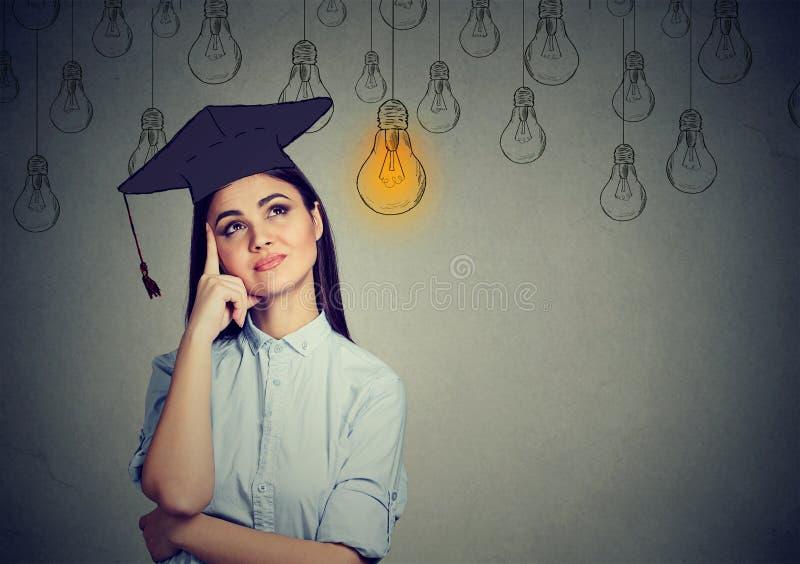 Mulher do aluno diplomado no vestido do tampão que olha acima no pensamento brilhante da ampola fotografia de stock